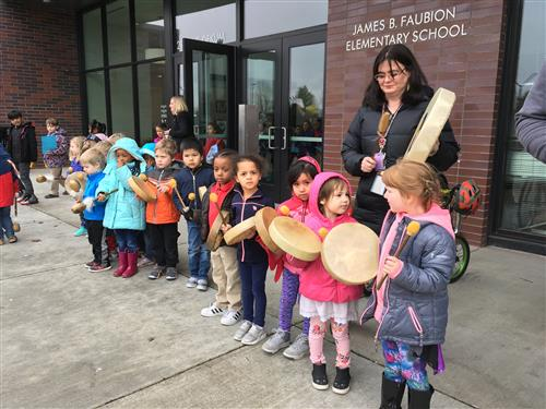 Students cheer on community marchers with drums