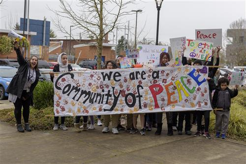 "Faubion and Concordia community members lead the Peach March with a large banner that reads ""We are a community of Peace"""