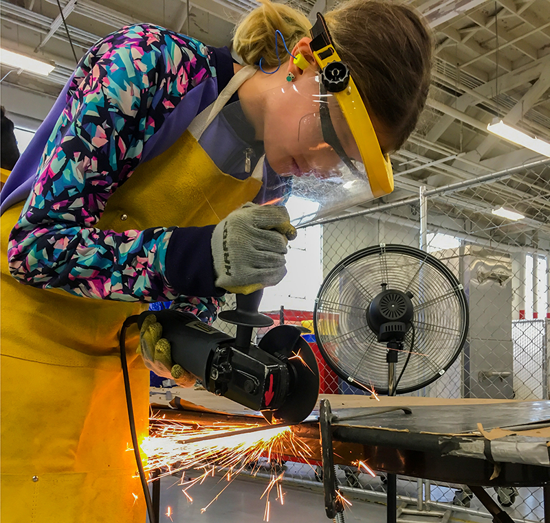 Female student standing at a work table using a grinder on some sheet metal, sparks flying.