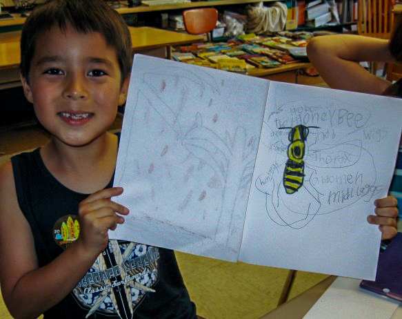 Native Maerican student holding up classwork, a drawing of a bee.