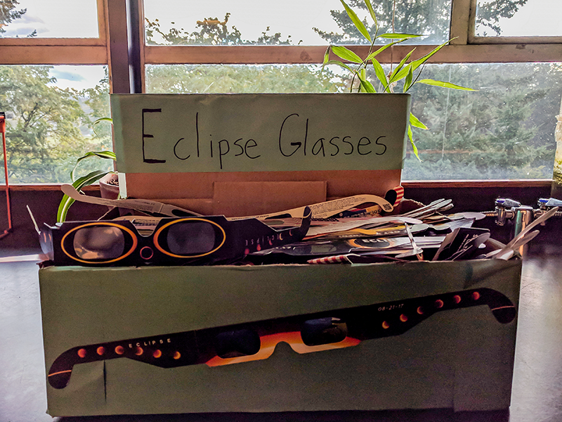 Box full of eclipse glasses on a window sill.
